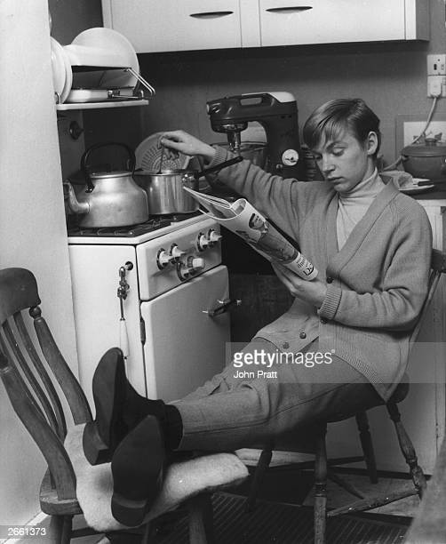 Pop singer Steve Perry reading a magazine while he waits for his supper to cook