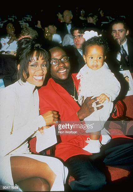 Pop singer Whitney Houston sitting w singer husband Bobby Brown who is holding their infant daughter Bobbi