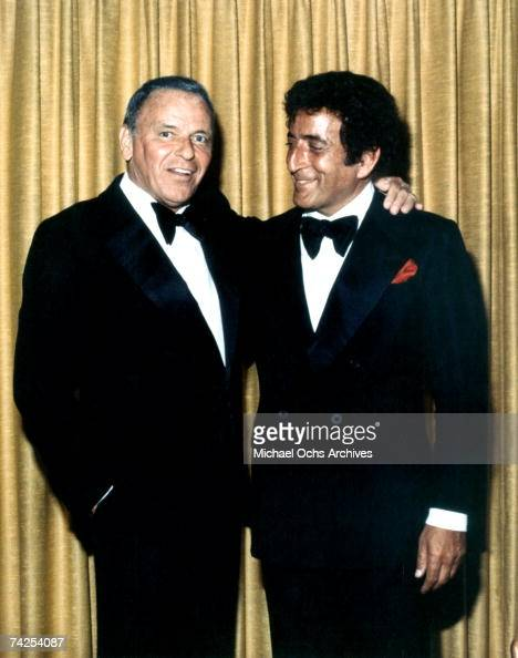 Pop singers Tony Bennett and Frank Sinatra pose for a portrait wearing tuxedos in front a of a gold curtain in July of 1980 in Reno Nevada