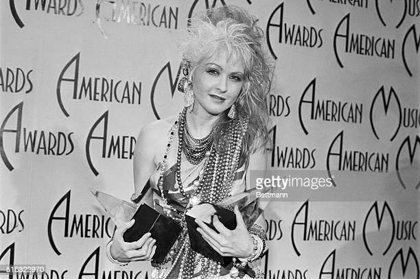 Pop star Cyndi Lauper holds her two American Music Awards which she won for Favorite Female Artist Pop/Rock and Favorite Female Video Artist Pop/Rock