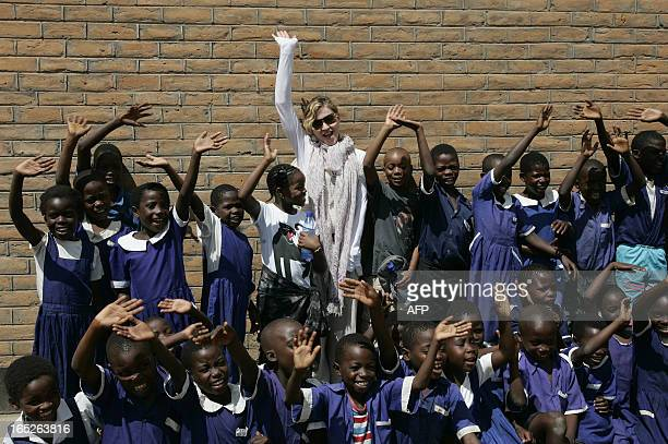 US Pop Star Madonna flanked by her Malawian adopted Children David and Mercy are pictured on April 2 2013 oustide of a classroom with school children...