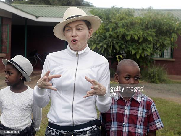 US Pop Star Madonna flanked by her Malawian adopted children David and Mercy speaks to media during her visit to Mphandula Children's Carecentre on...
