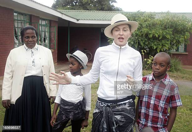 US Pop Star Madonna flanked by her Malawian adopted children David right and Mercy and Yasinta Chapomba Executive Director for Mphandula Childcare...