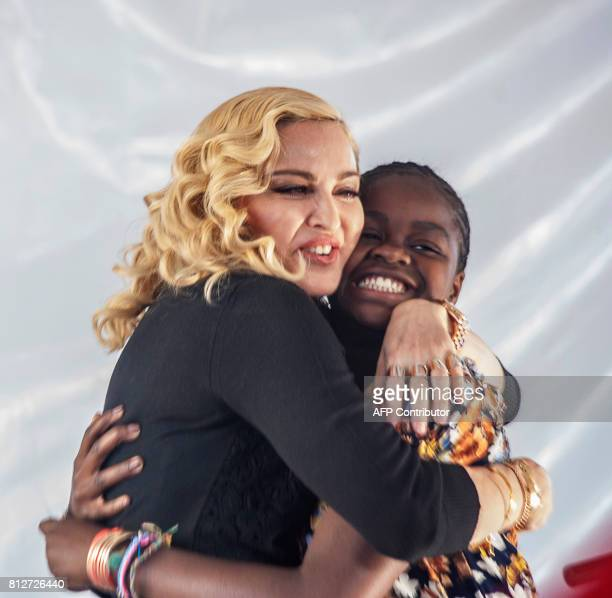 TOPSHOT US pop star Madonna hugs her Malawian adopted daughter Mercy James after she made a speech during the opening ceremony of the Mercy James...