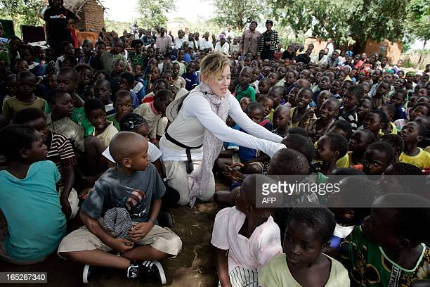 US Pop Star Madonna interacts with Malawian children at Mkoko Primary School on April 2 2013 in the region of Kasungu central Malawi one of the...