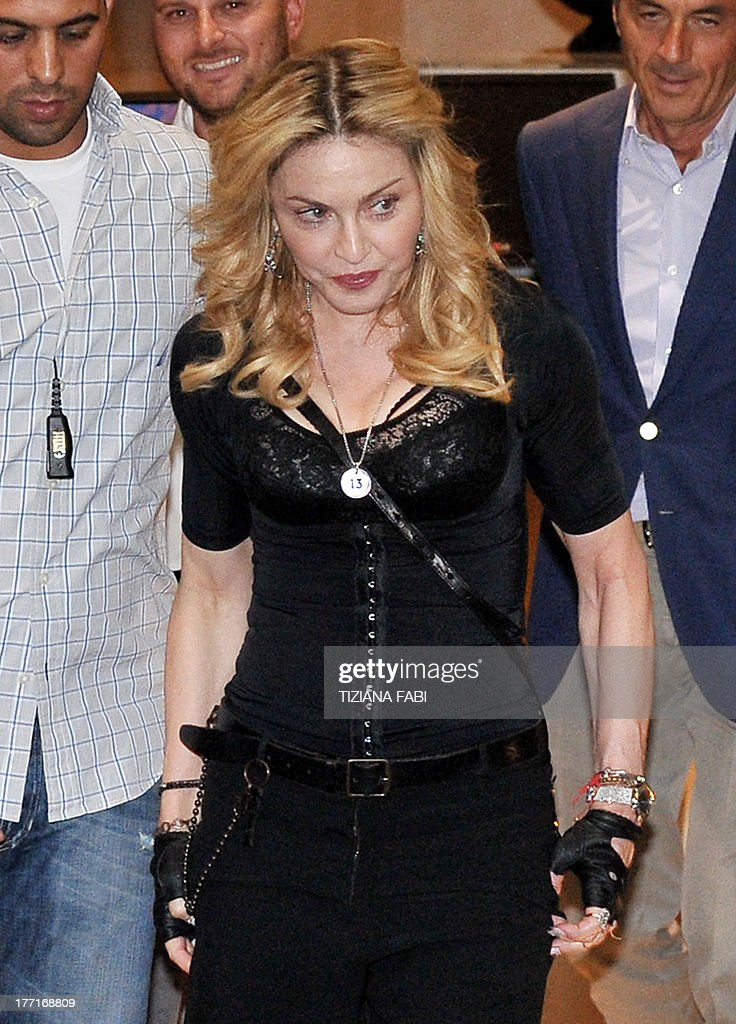 US pop star Madonna leaves after visiting a Hard Candy Fitness center in central Rome on August 21, 2013. The fitness clubs are part of a global chain she and her business partners are unveiling around the world. AFP PHOTO / TIZIANA FABI