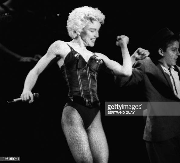 US pop star Madonna performs along with an unidentified dancing partner 28 August 1987 during a single concert held in the park of the town of Sceaux...