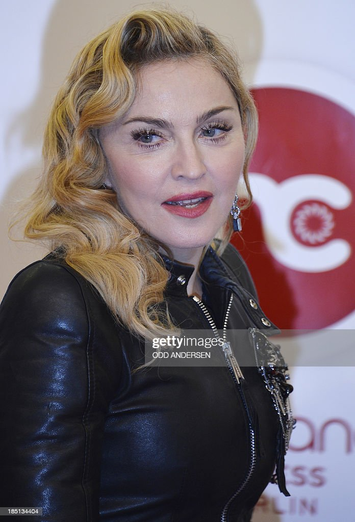US pop star Madonna poses for photographers on the red carpet on the opening event of the Fitness Center 'Hard Candy' on October 17, 2013 in Berlin.The fitness club is part of a global chain Madonna is unveiling around the world.