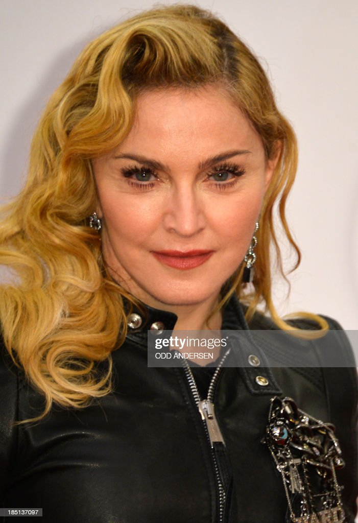 US pop star Madonna poses for photographers on the red carpet on the opening event of the Fitness Center 'Hard Candy' on October 17 2013 in Berlin...