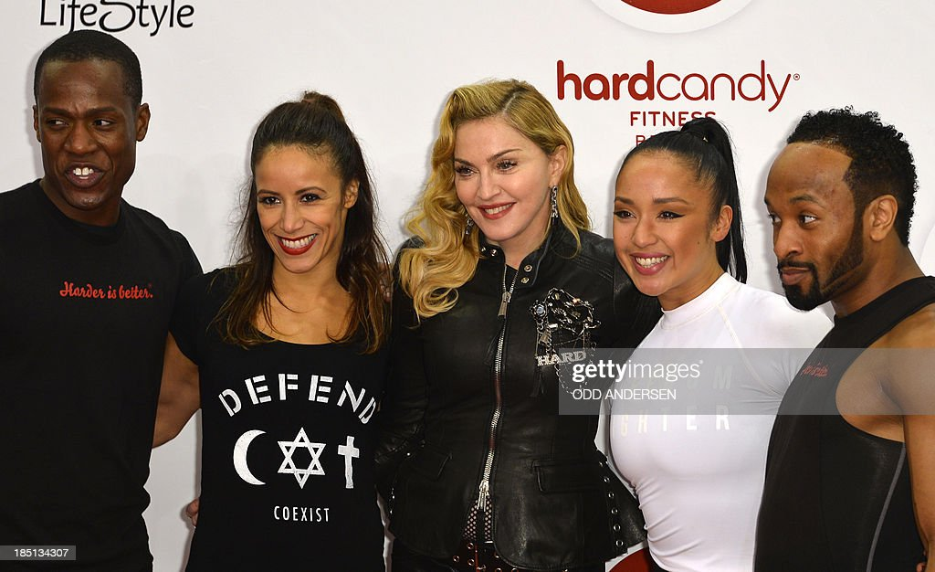 US pop star Madonna (3rd L) poses for photographers with her personal trainer Nicole Winhoffer (4rd L) and staff on the red carpet on the opening event of the Fitness Center 'Hard Candy' on October 17, 2013 in Berlin.The fitness club is part of a global chain Madonna is unveiling around the world. AFP PHOTO / ODD ANDERSEN