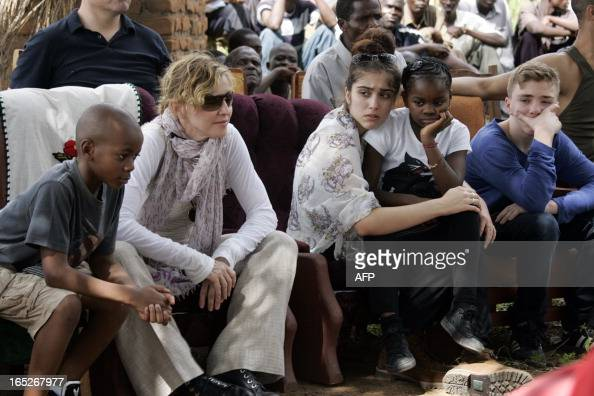 US Pop Star Madonna sits with her biological and adopted children David Banda Lourdes Mercy James and Rocco at Mkoko Primary School one of the...