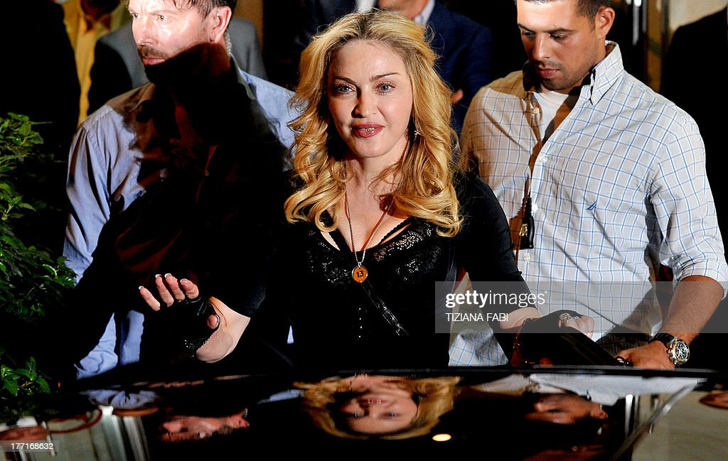 US pop star Madonna waves after visiting a Hard Candy Fitness center in central Rome on August 21, 2013. The fitness clubs are part of a global chain she and her business partners are unveiling around the world.