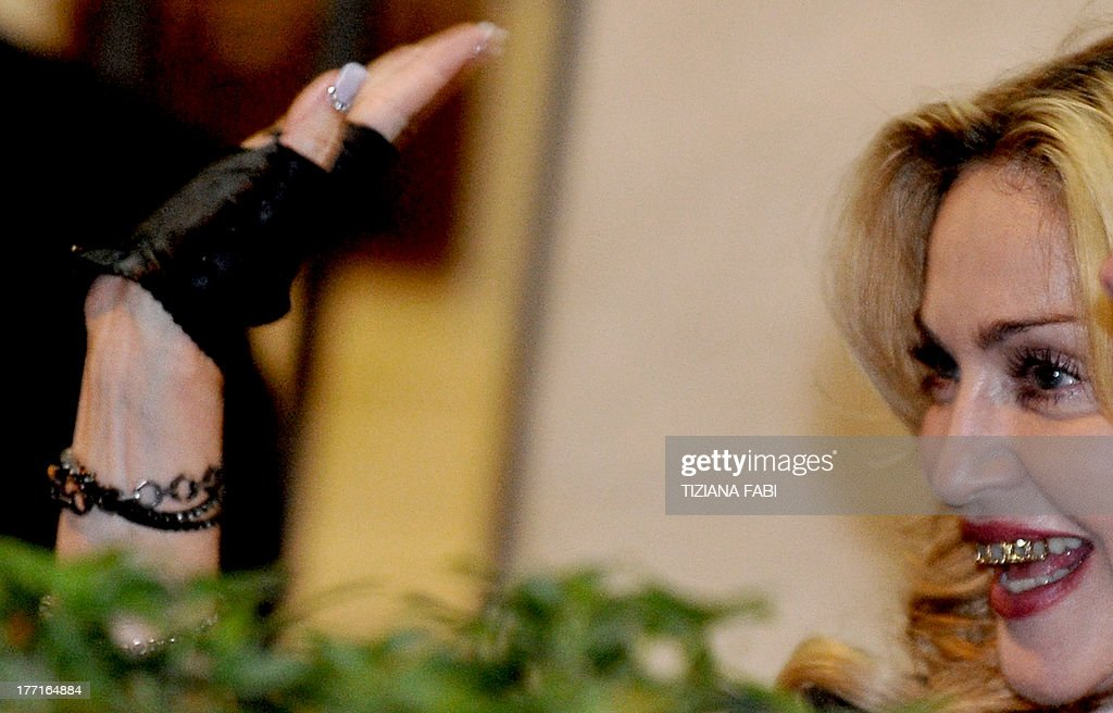 US pop star Madonna waves as she arrives to visit a Hard Candy Fitness center in central Rome on August 21, 2013. The fitness clubs are part of a global chain she and her business partners are unveiling around the world.