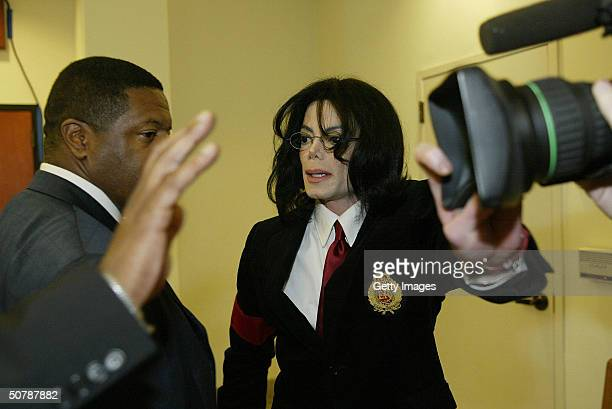 Pop star Michael Jackson and his bodyguard cover the lens of a camera to avoid being filmed as he enters the Santa Maria Courthouse April 30 2004 in...