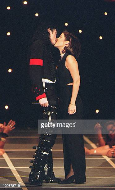 US pop star Michael Jackson and his wife Lisa Marie Presley kiss on the stage of Radio City Music Hall 8 September 1994 in New York where they...