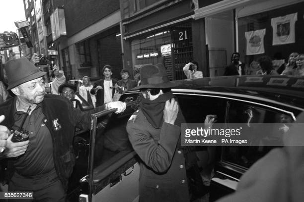 Pop star Michael Jackson covers his face with a scarf as he leaves his black limousine to go shopping in Hamley's toy shop in Regent Street