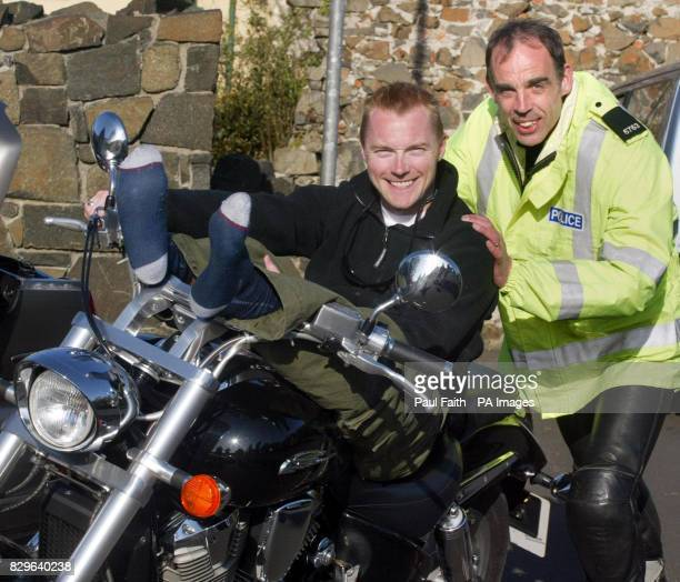 Pop star Ronan Keating rests on a motorbike at Bushmills in County Antrim accompanied by Police constable Stevie Nugent after completing the first...
