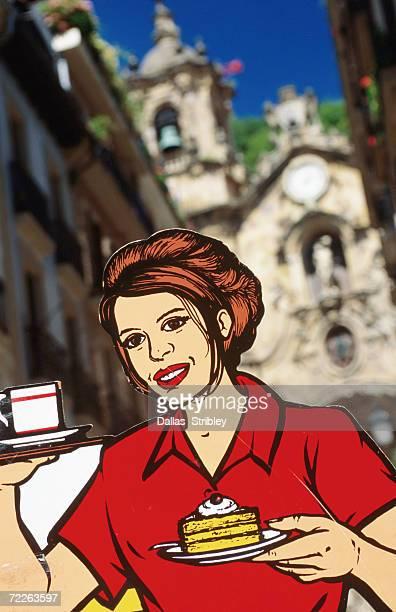 Pop-art waitress sign with Iglesia de Santa Maria in background, San Sebastian, Spain