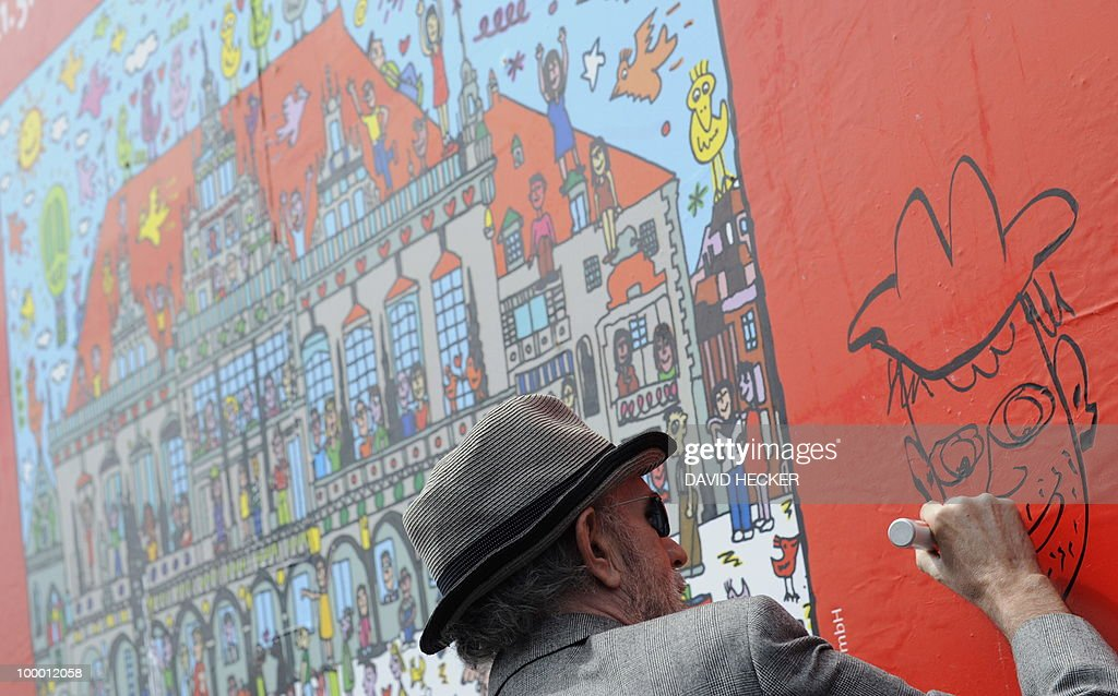 US pop-artist James Rizzi paints on a poster designed by him during a press preview of the exhibition 'Rizzi's World' on May 20, 2010 in Bremen, northern Germany. From May 21 to July 4, 2010, the Messehallen Bremen present a retrospective with more than 1,200 works of the artist.