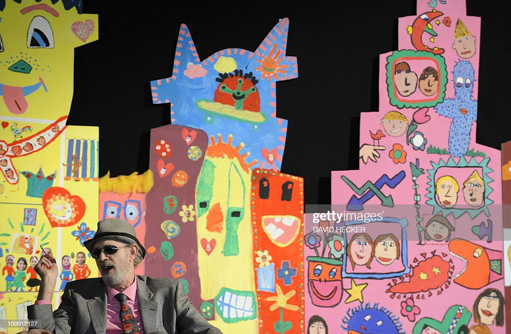US pop-artist James Rizzi sits in front of paintings by children from Bremen as he gives an interview on the exhibition 'Rizzi's World' on May 20, 2010 in Bremen, northern Germany. From May 21 to July 4, 2010, the Messehallen Bremen present a retrospective with more than 1,200 works of the artist.