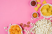 Fresh popcorn, snacks and chips in a bowl isolated on pink background top view. Frame composition with copy space. Movie watching concept