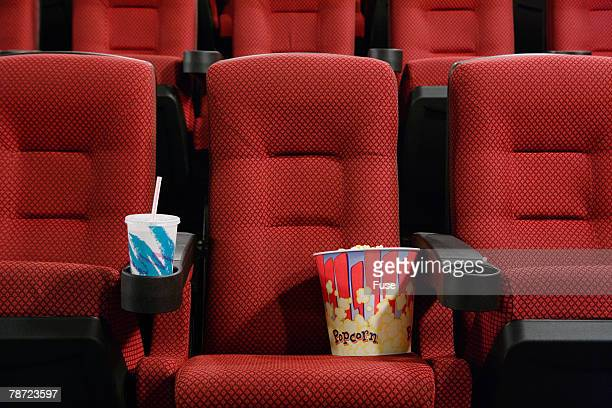 Popcorn and Soft Drink in Empty Seat at the Movie Theater
