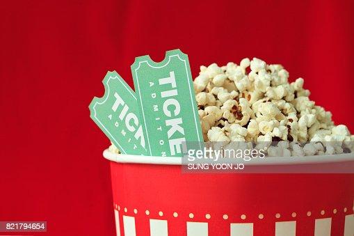 Bolso de las palomitas y la entrada de película sobre fondo rojo : Foto de stock