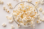 Glass bowl of popcorn isolated on white background. Fast food, cinema snack and entertainment concept, cutout, closeup texture, above view