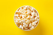 Popcorn bowl viewed from above on yellow background. Flat lay. Top view