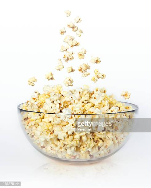 Popcorn falling into a full glass bowl on a blank background
