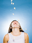 popcorn falling into the open mouth of a young woman