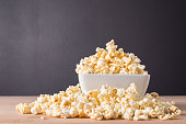 Popcorn in white bowl on wooden background