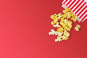 Popcorn spill out from popcorn paper bag on red background