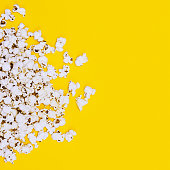 Popcorn on yellow background. Minimalism fashion detail.