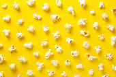 Popcorn pattern on yellow background. Top view