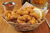 a basket of popcorn shrimp with lemon and cocktail sauce with a mug of beer