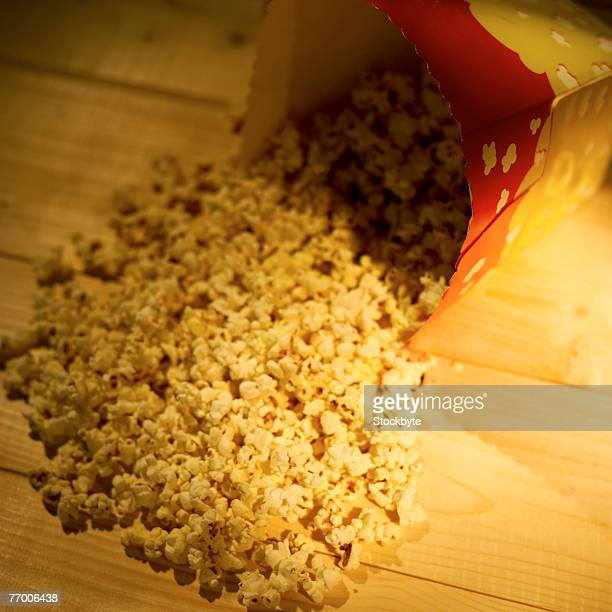 Popcorn spilling from container onto wooden table