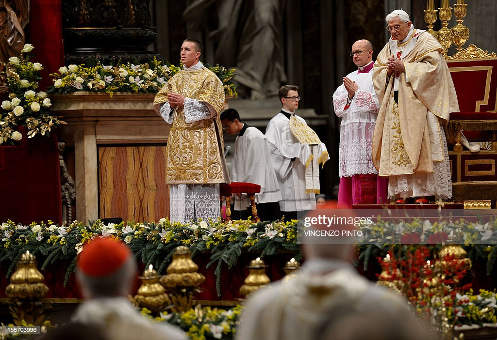 Pope Benedict XVI (R) celebrates Christmas mass at St. Peter's Basilica to mark the nativity of Jesus Christ, in Vatican City on December 24, 2012.