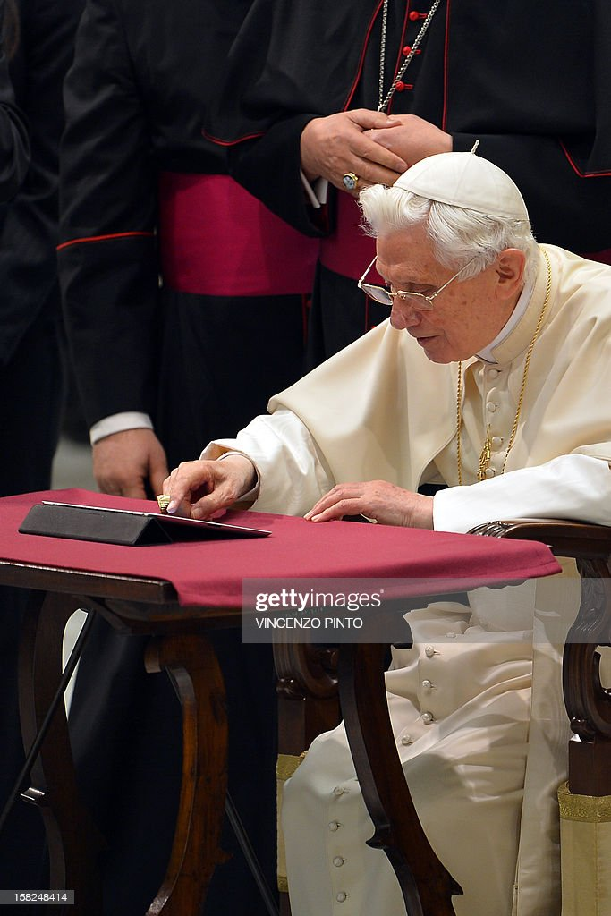 Pope Benedict XVI clicks on a tablet to send his first twitter message during his weekly general audience on December 12, 2012 at the Paul VI hall at the Vatican. Pope Benedict XVI sent his first Twitter message from a digital tablet on Wednesday using the handle @pontifex, blessing his hundreds of thousands of new Internet followers.
