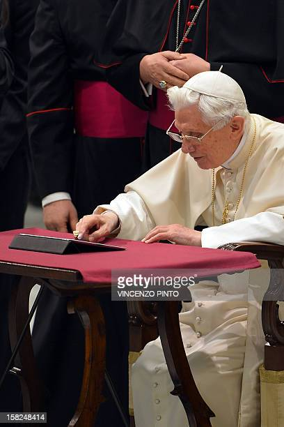 Pope Benedict XVI clicks on a tablet to send his first twitter message during his weekly general audience on December 12 2012 at the Paul VI hall at...