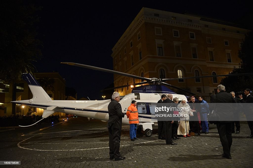 Pope Benedict XVI (C, in white) disembarks from a helicopter as he arrives for his visit at the Pontificio Seminario Romano Maggiore in Rome, on February 8, 2013.