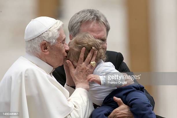Pope Benedict XVI flanked by his personal secretary Georg Ganswein kisses a baby during his weekly audience in St Peter's Square on May 23 2012 in...