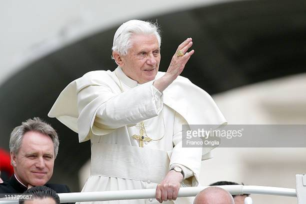 Pope Benedict XVI flanked by his personal secretary Monsignor Georg Gaenswein waves to the faithful gathered in St Peter's Square during his weekly...