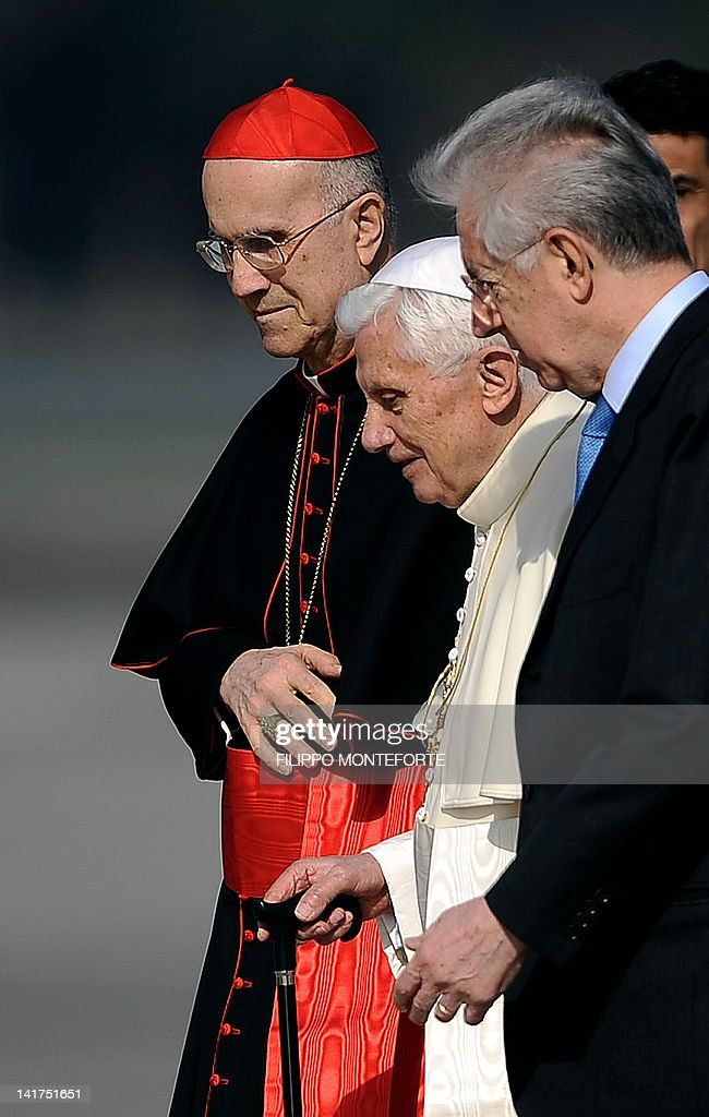 Pope Benedict XVI flanked by Vatican secretary of state Cardinal Tarcisio Bertone and Italian Premier Mario Monti walks on the tarmac as he boards a...