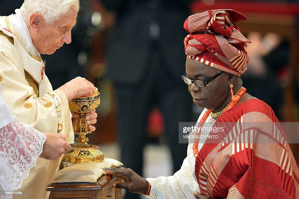 Pope Benedict XVI (L) gives the holy communion to a Nigerian faithful during a Holy mass with new cardinals on November 25, 2012 at St Peter's basilica at the Vatican. Pope Benedict XVI the day before consecrated six non-European prelates as new members of the College of Cardinals in a development welcomed by critics concerned that the body which will elect the future pope is too Euro-centric. AFP PHOTO / VINCENZO PINTO