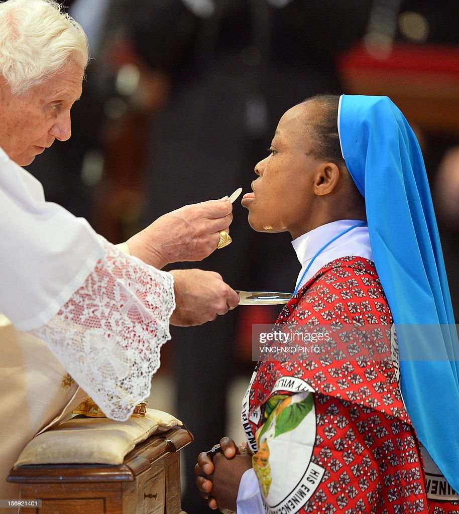 Pope Benedict XVI (L) gives the holy communion to a Nigerian nun during a Holy mass with new cardinals on November 25, 2012 at St Peter's basilica at the Vatican. Pope Benedict XVI the day before consecrated six non-European prelates as new members of the College of Cardinals in a development welcomed by critics concerned that the body which will elect the future pope is too Euro-centric. AFP PHOTO / VINCENZO PINTO
