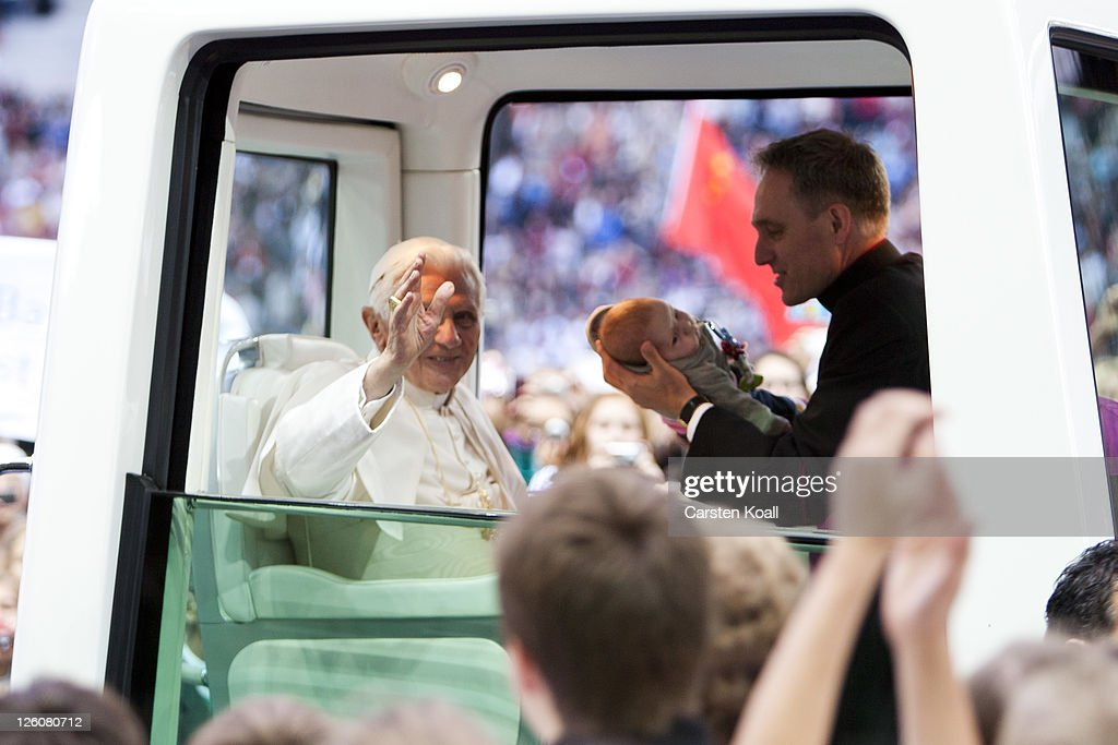 Pope Benedict XVI greets visitors while his assistent Georg Gaenswein (R) shows a baby during riding in the Popemobile upon his arrival at Olympiastadion stadium, where he later gave a Catholic mass for 70,000 people, on September 22, 2011 in Berlin, Germany. Pope Benedict, who is German, is in Berlin on the first of a four-day visit to Germany.