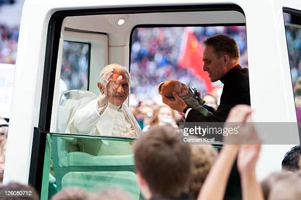 Pope Benedict XVI greets visitors while his assistent Georg Gaenswein shows a baby during riding in the Popemobile upon his arrival at Olympiastadion...