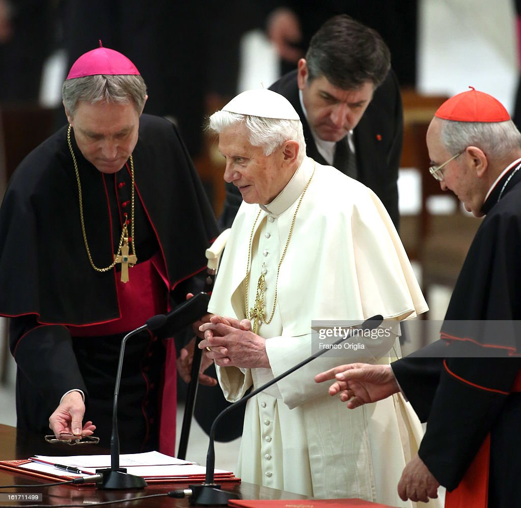 Pope Benedict XVI, his assisted by cardinal Agostino Vallini (R), his personal secretary Georg Ganswein (L) and his new butler Sandro Mariotti (C), as he attends a meeting with parish priests of Rome's diocese at the Paul VI Hall on February 14, 2013 in Vatican City, Vatican. The Pontiff will hold his last weekly public audience on February 27 at St Peter's Square after announcing his resignation earlier this week.
