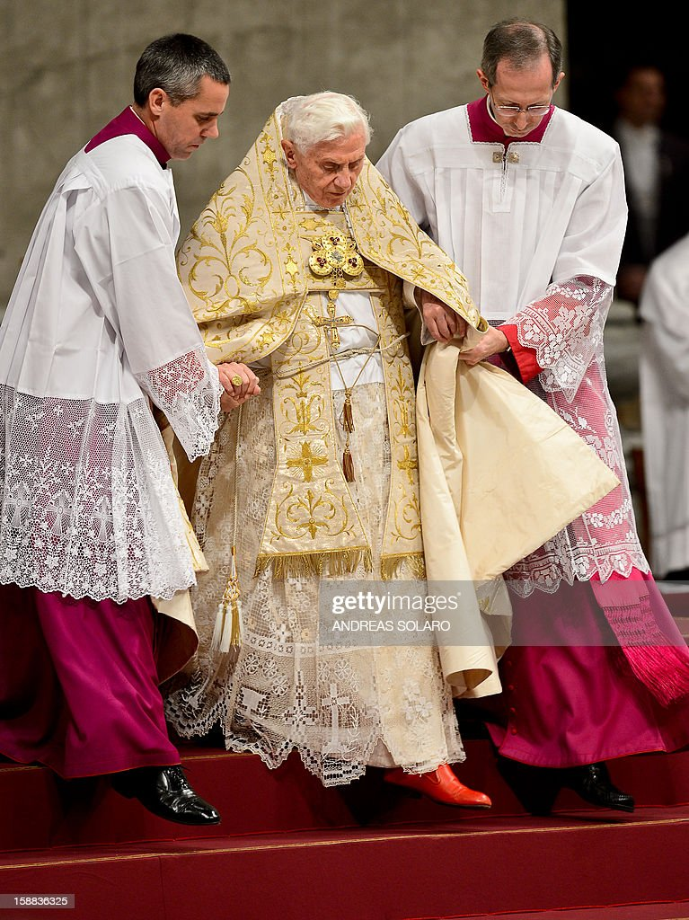 Pope Benedict XVI is helped by assistants as he celebrates the Vespers and Te Deum prayers in Saint Peter's Basilica at the Vatican on December 31, 2012. AFP PHOTO / ANDREAS SOLARO